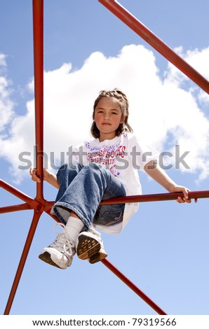 A cute young girl climbs up high on a jungle gym at a playground. - stock photo