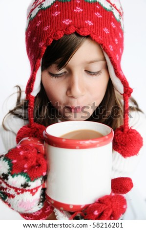 A cute young girl drinking hot cocoa - stock photo