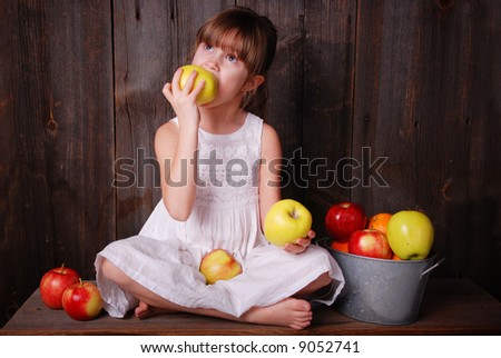 A cute young girl eating an apple - stock photo