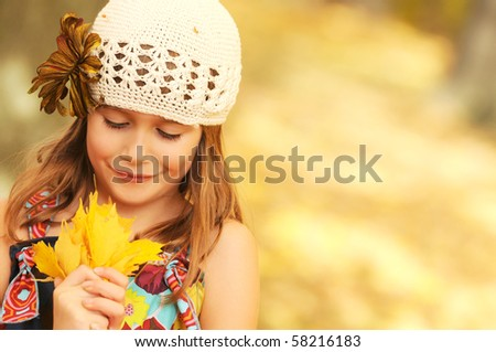 A cute young girl holding a hand-full of leaves - stock photo