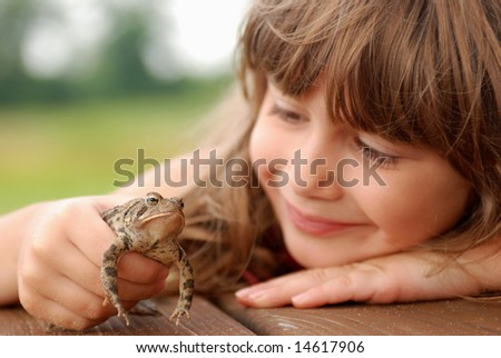 A cute young girl holding a toad - stock photo