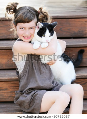 A cute young girl holding her kitty - stock photo