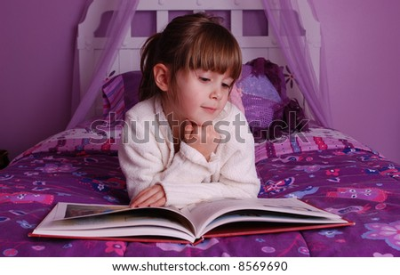 A cute young girl lying on her bed reading a book - stock photo