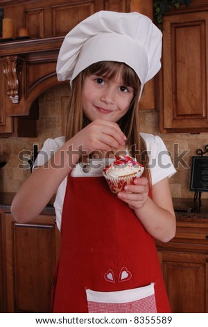 A cute young girl putting sprinkles on her cupcake - stock photo