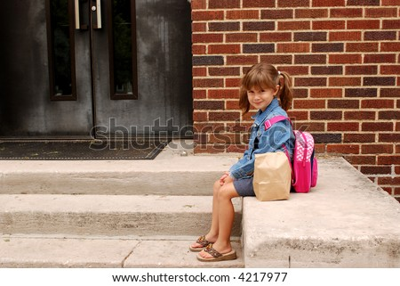 A cute young girl ready for her first day of school - stock photo