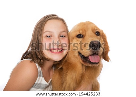 A cute young girl sits with her handsome golden retriever dog