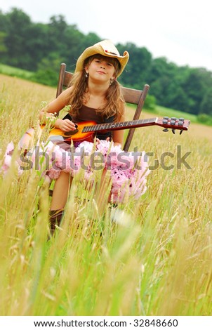 A cute young girl sitting in a field playing the guitar - stock photo