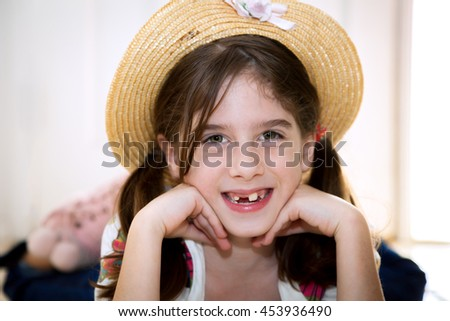 A cute, young, snaggletooth girl smiles with her chin on her hands.  She is wearing a straw hat and laying on her stomach. - stock photo