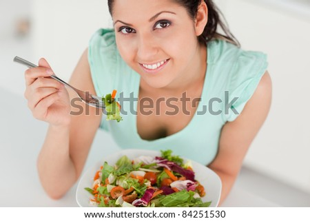 A cute young woman eating a salad