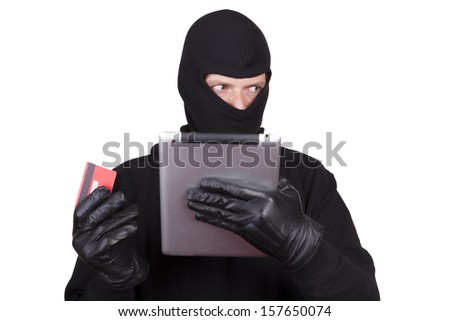 A cyber criminal committing Internet Theft. Man wearing a balaclava and holding a credit card and a tablet computer, white background.  - stock photo