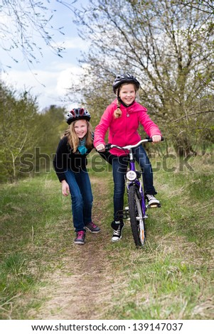 A cycling girls in front of rural landscape