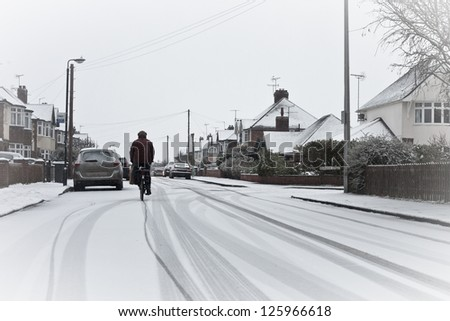A cyclist on a snowy residential road in England - stock photo