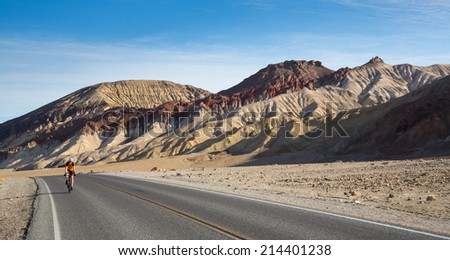 A cyclist rides in the spring heat in Death Valley National Park, California. - stock photo