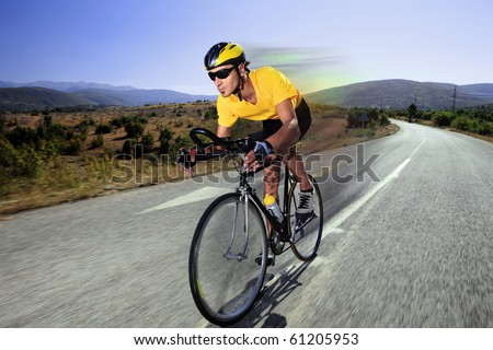 A cyclist riding a bike on an open road in Macedonia - stock photo