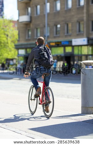 A cyclist riding on a street in the summer time. - stock photo