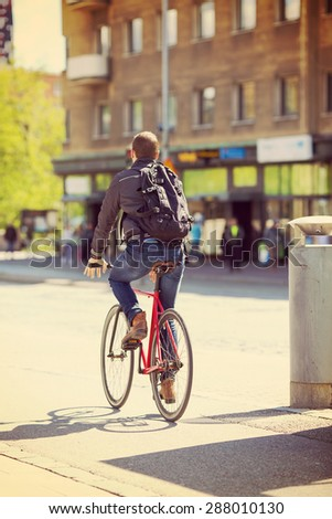 A cyclist riding on a street in the summer time. Image has vintage effect. - stock photo