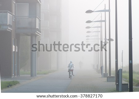 A cyclist riding through the fog - stock photo