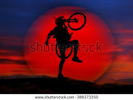A cyclist travels through alpine hills and stands against a background of sunset with a mountain bike - MTB as a symbol. Extreme sports are dangerous in the mountains,  require high skill and training - stock photo