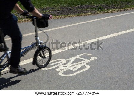 A Cyclist using a Cycle Path in Hyde Park in London. - stock photo