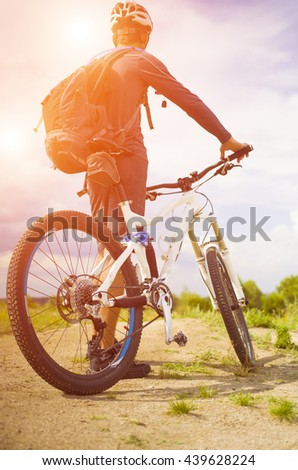 A cyclist with a backpack on a background of blue sky and the road. - stock photo