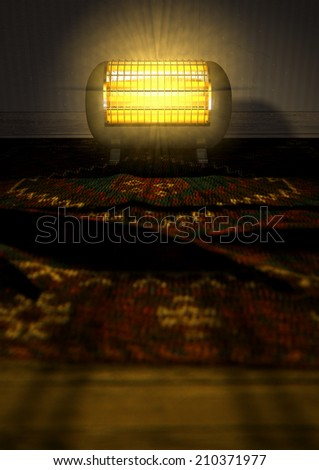 A cylindrical shaped electrical heater illuminated and radiating in an old room on a vintage red persian rug