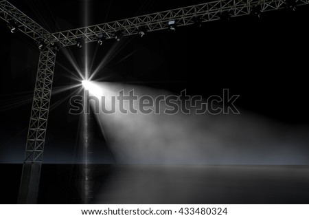 A 3D render of an empty music concert stage in darkness lit by a single spotlight - stock photo
