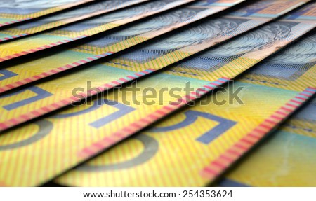 A 3D rendering of a macro close-up view showing the detail of australian dollar banknotes laid out and overlapping in a staggered row - stock photo