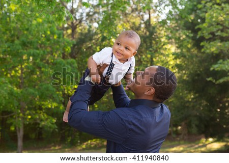 A dad holding his son - stock photo