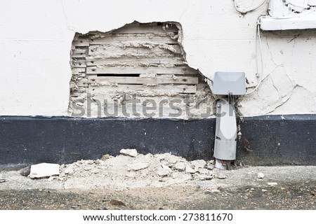 A damaged area on an external house wall with exposed plaster and wood
