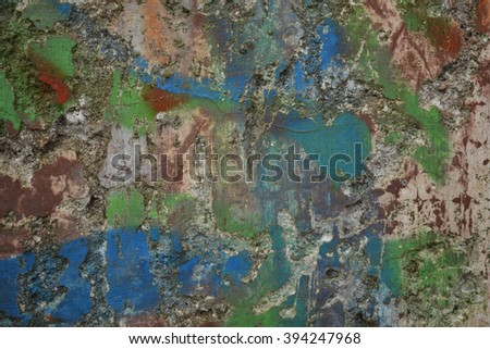 a damaged plaster wall with colourful paint remnants - stock photo