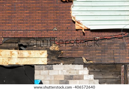 A damaged wall on a building that has many layers. There is wood, false brick, stone, siding, tar paper, and more.  The layers are peeling away. - stock photo