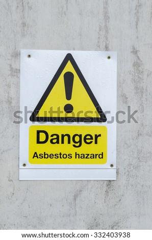 A danger sign for asbestos hazard, England UK. - stock photo
