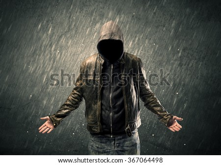 A dangerous unrecognizable faceless criminal standing in front of grainy urban wall concept - stock photo