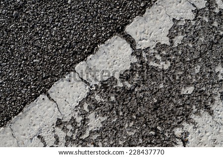 A dark asphalt pavement texture with old and grunge horizontal traffic sign painted with white reflective color