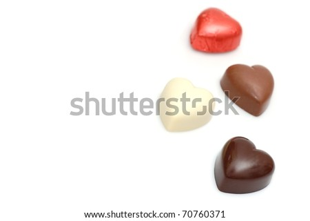 A Dark Chocolate Valentine's Heart in the Foreground with Three More Chocolate Hearts in the Background with Room for Text - stock photo