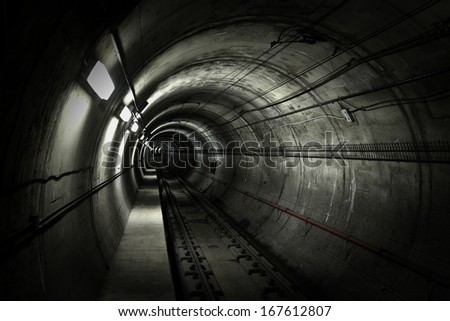 A dark grungy subway tunnel with tracks.