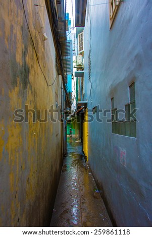 A dark, narrow alley between two buildings in the Pham Ngu Lao district of Ho Chi Minh City, Vietnam. The building facades are a colorful blue and yellow, and the paint is chipped and peeling. - stock photo