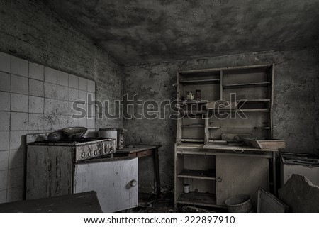 A dark, shabby kitchen in a dilapidated, abandoned house. - stock photo