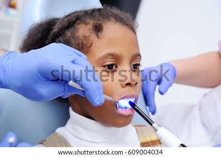 a dark-skinned baby girl in the dentist's chair.dentist shines a UV lamp at the little patient's teeth.