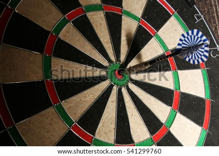 A dart arrow stick on the center of dart board.. bull eye!!
