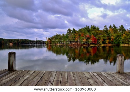 A Day At the Lake. Dock overlooking a lake with an island ablaze in autumn color. Ludington State Park. Ludington, Michigan. - stock photo