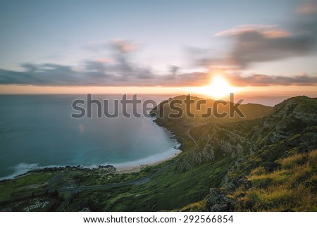 A day time long exposure of sunrise as seen from a ridge overlooking the eastern point of Oahu, Hawaii. The intentional motion blur in the clouds creating the illusion that they are moving.  - stock photo