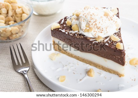 A decadent haupia and chocolate custard pie topped with shaved coconut, macadamia nuts and shaved chocolate, served with whipped cream - stock photo