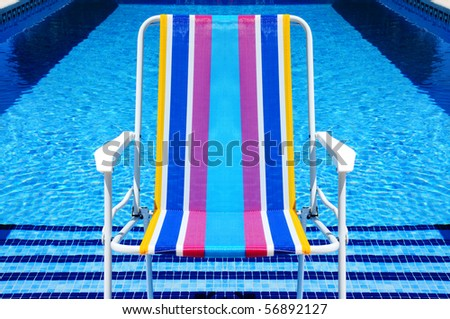 a deckchair in a swimming pool in the summer - stock photo