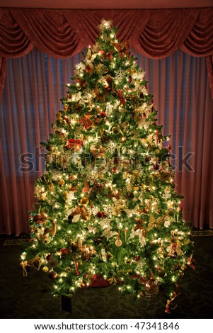 A decorated and lighted indoor Christmas tree