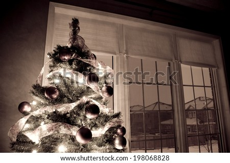 A decorated and lit Christmas tree near a window. - stock photo