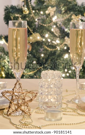 A decorated christmas dining table with champagne glasses and christmas tree in background - stock photo