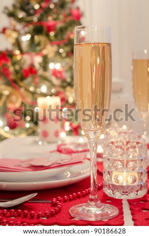 A decorated christmas dining table with champagne glasses and christmas tree in background
