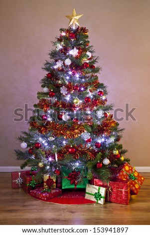 A decorated Christmas tree in a home, lit up with fairy lights and surrounded by gift wrapped presents.