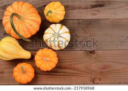 A decorative autumn still life of mini pumpkins and gourds on a rustic wood table. Horizontal format with copy space. - stock photo